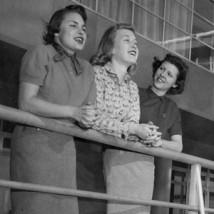 Three 1950s women leaning on railing
