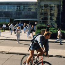 1990s man riding bike outside Union by students walking