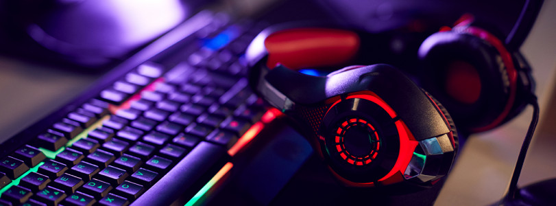 red and black gaming headset next to keyboard with multicolored lighting