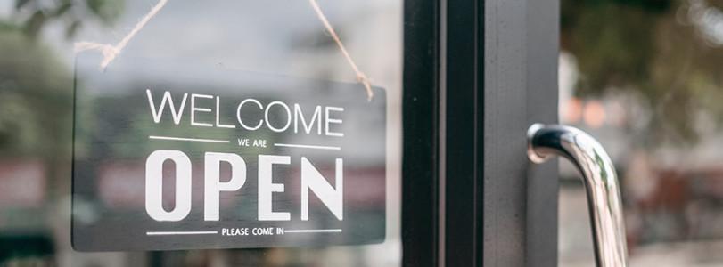 """""""Welcome, Open"""" sign on generic store door"""