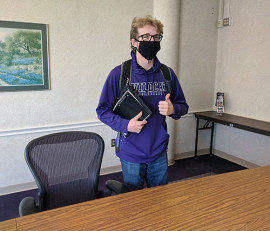 masked student standing in study room
